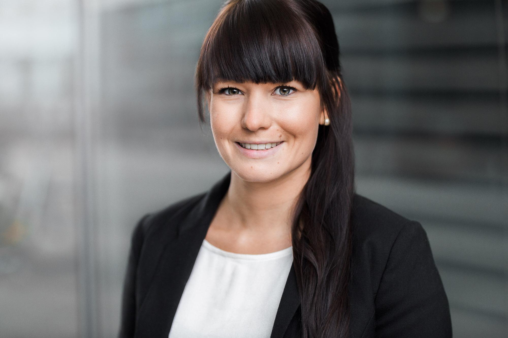 Dieses Bewerbungsfoto wurde von Tom und Lia Fotografie aus Rostock aufgenommen. Es zeigt eine junge Frau, im Hintergrund ist die Fassade der Deutschen Med zu sehen.