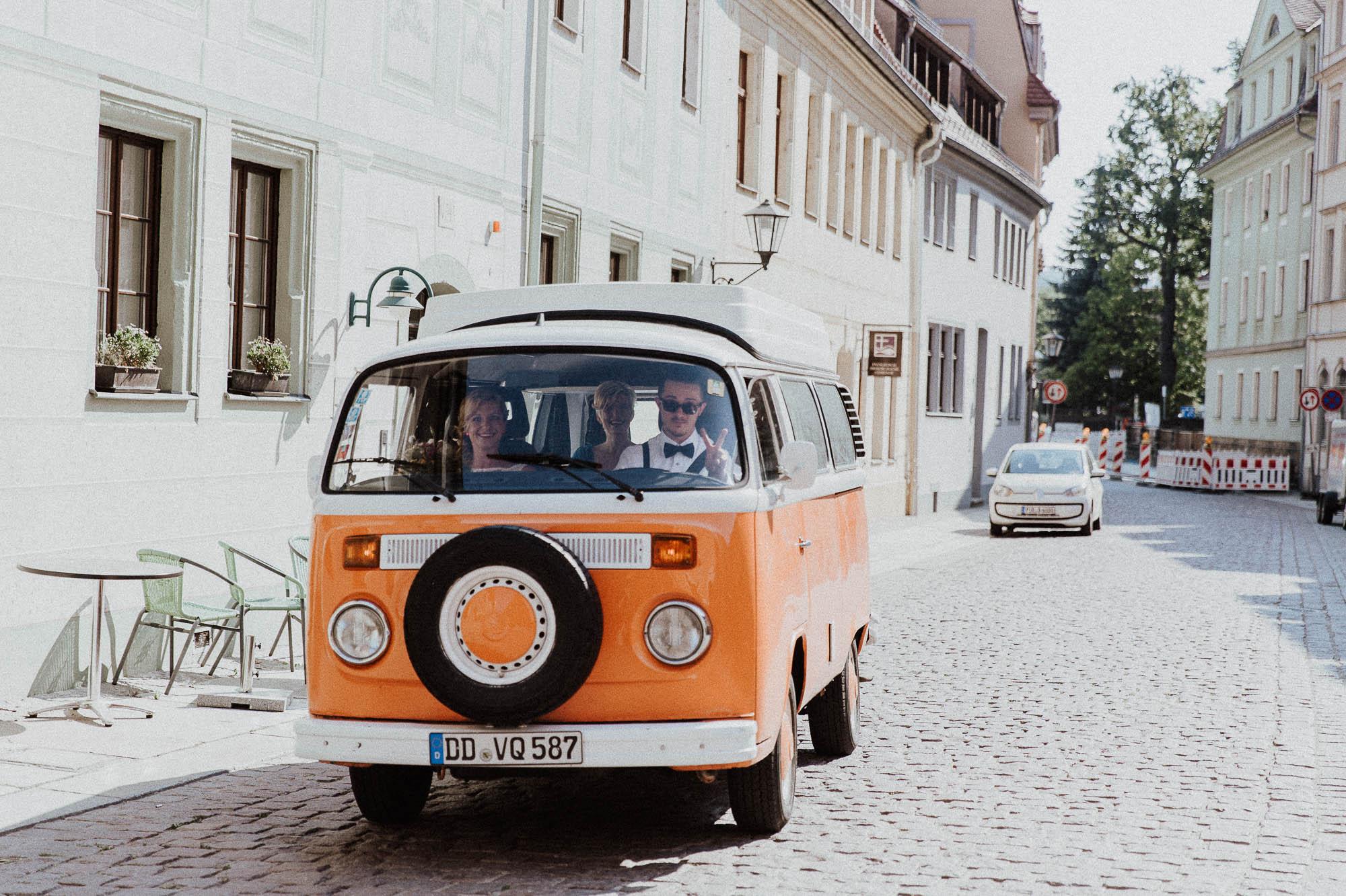 Gezeigt wird ein VW Bulli in Orange, in dem ein Hochzeitspaar sitzt.