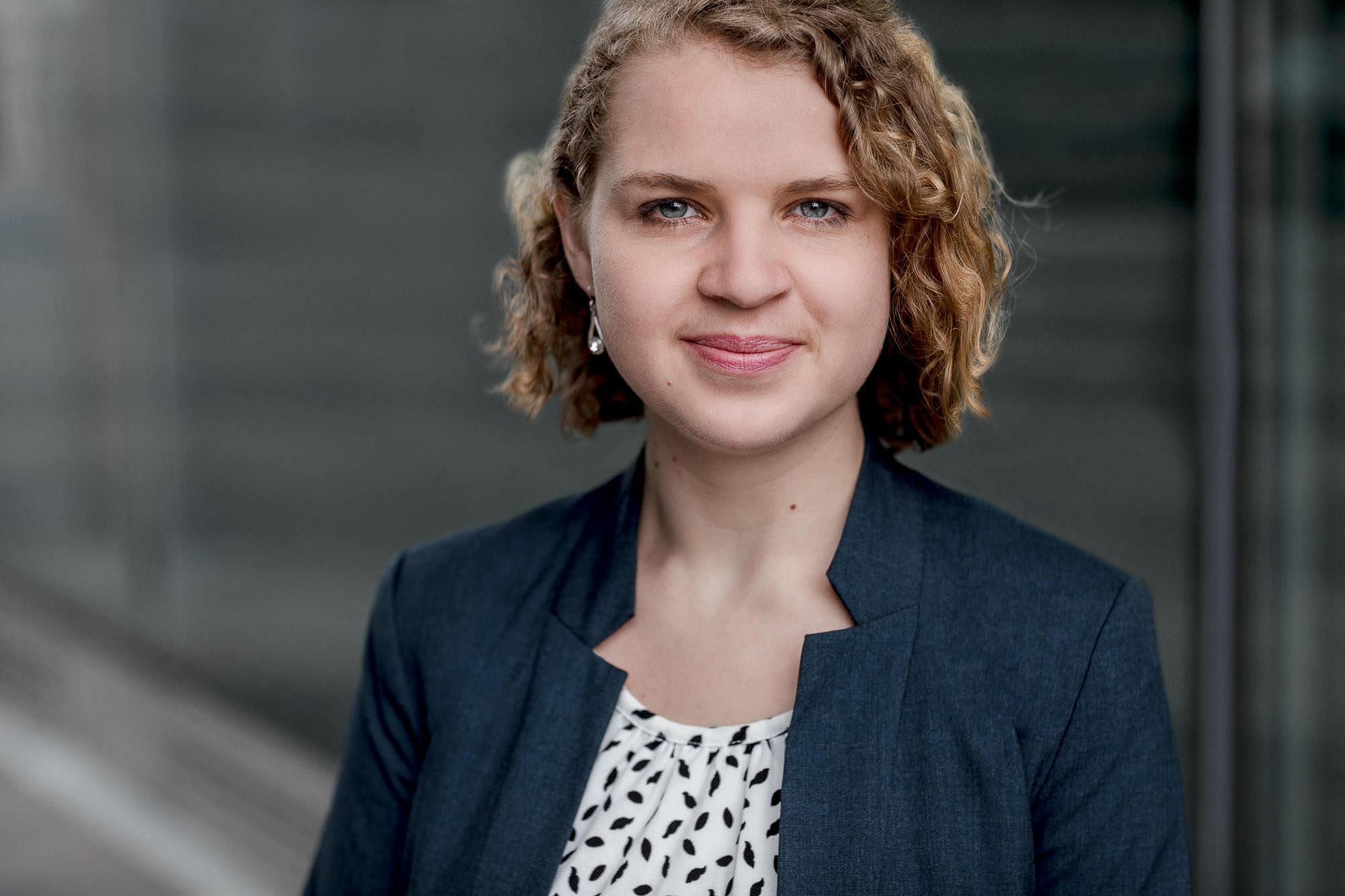 Dieses Bewerbungsfoto wurde von den Fotografen Tom und Lia aus Rostock aufgenommen. Zu sehen ist eine junge Frau vor der Deutschen Med, ein Gebäude im Zentrum von Rostock. Die Fassade des Gebäudes eignet sich sehr gut für professionelle Bewerbungsfotos.