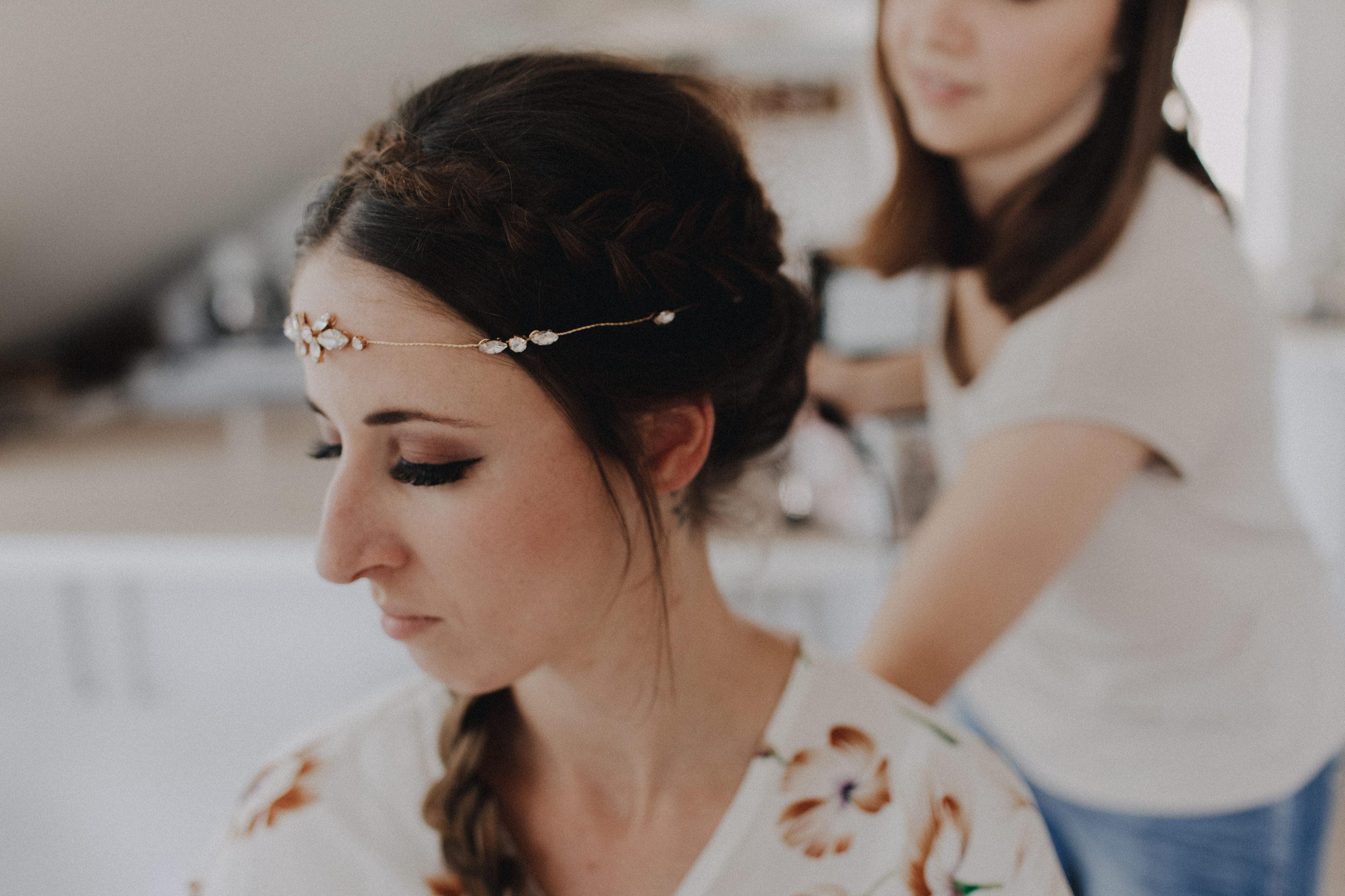 Dieses Foto ist Teil einer Hochzeitsreportage, die von den Hochzeitsfotografen Tom und Lia aus Potsdam aufgenommen wurde. Zu sehen ist die Braut, die während des Getting Readys geschminkt und angezogen wird.