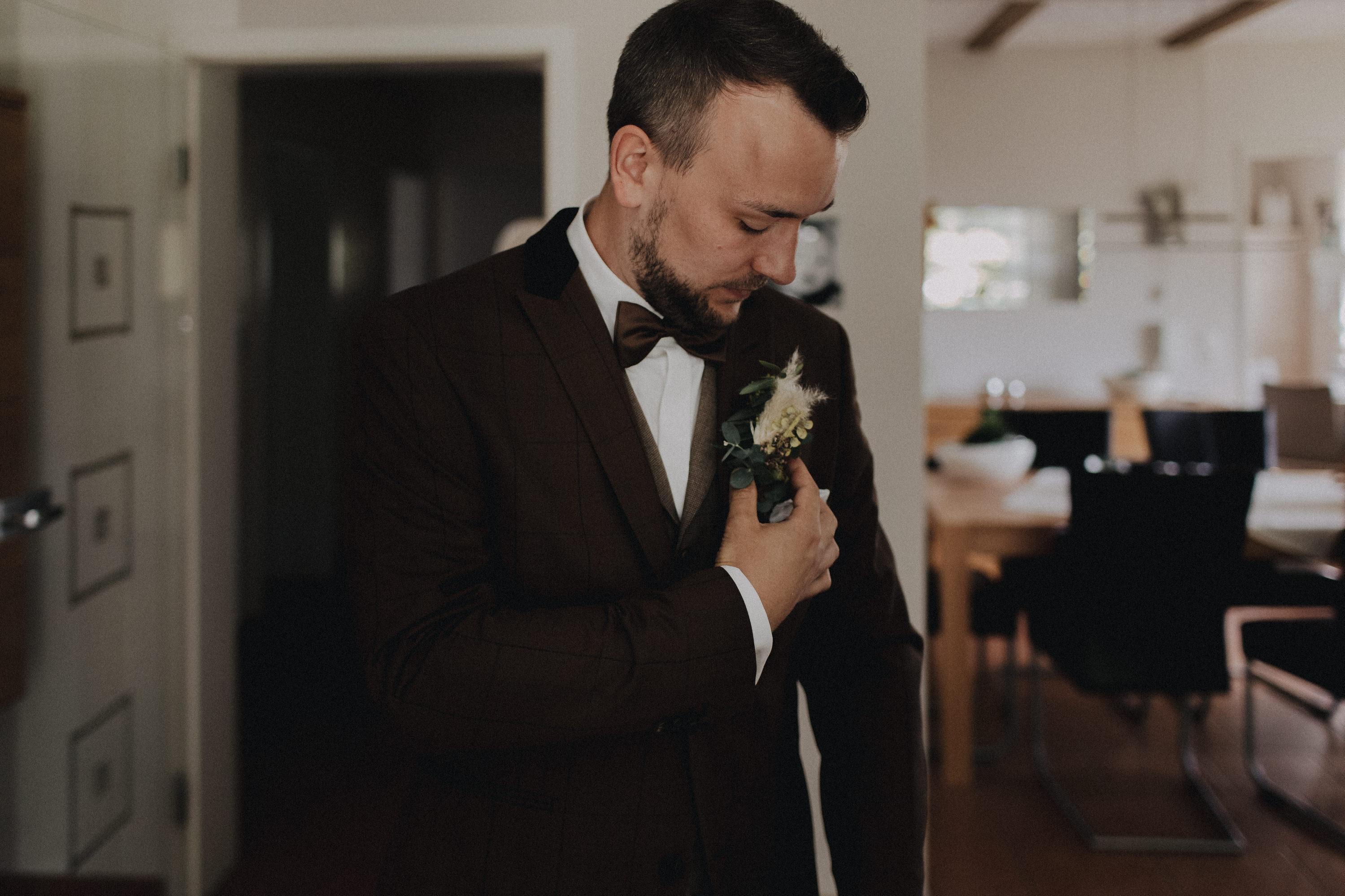 Dieses Foto ist Teil einer Hochzeitsreportage, die von den Hochzeitsfotografen Tom und Lia aus Potsdam aufgenommen wurde. Zu sehen ist der Bräutigam während des Getting Readys, der sich mit seinen besten Freunden anzieht.