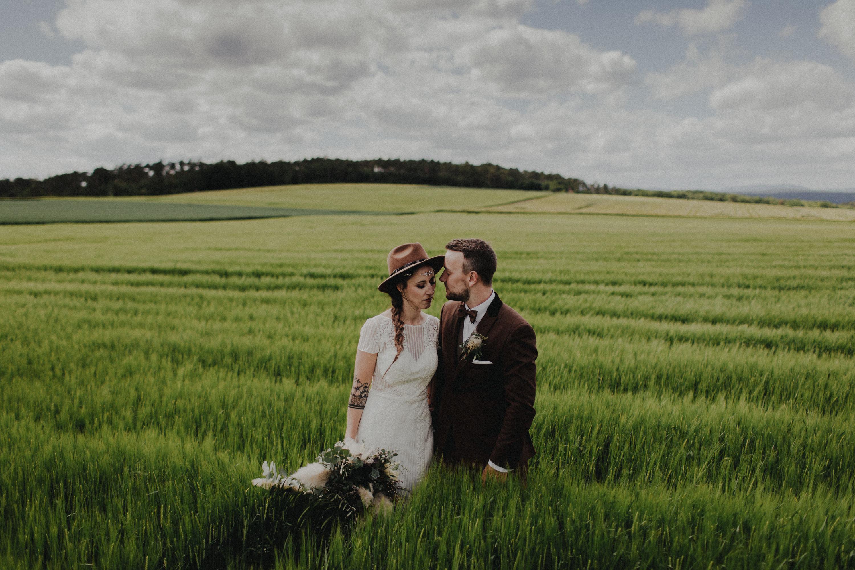 Dieses Foto ist Teil einer Hochzeitsreportage, die von den Hochzeitsfotografen Tom und Lia aus Potsdam aufgenommen wurde. Zu sehen ist das Brautpaar während des Brautpaar-Shootings in einem satt grünem Feld bei strahlendem Sonnenschein.